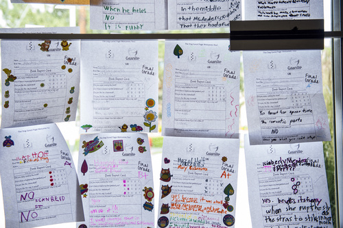 Chris Detrick  |  The Salt Lake Tribune Completed book report cards hang on the window as a part of the Play Unplugged program at The Dog-Eared Page in Holladay Tuesday, June 24, 2014. Play Unplugged is a summer program that gives kids incentives to do other activities besides watching TV or playing video games. For every activity they complete, they receive a badge.