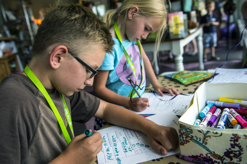 Chris Detrick  |  The Salt Lake Tribune Isaac Raymond, 11, and Abigail Raymond, 7, fill out their book report cards as a part of the Play Unplugged program at The Dog-Eared Page in Holladay Tuesday, June 24, 2014. Play Unplugged is a summer program that gives kids incentives to do other activities besides watching TV or playing video games. For every activity they complete, they receive a badge.
