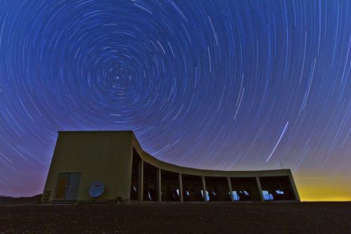 Ben Stokes | University of Utah  In this time-lapse photo, stars appear to rotate above the Middle Drum facility of the Telescope Array, a $25 million cosmic ray observatory that sprawls across the desert west of Delta, Utah. Physicists from the University of Utah, University of Tokyo and elsewhere report the observatory has detected a ìhotspotî in the northern sky emitting a disproportionate number of ultrahigh-energy cosmic rays, which are the most energetic particles in the universe. The  discovery of a hotspot is a step in the long quest to discover the source or sources of the most powerful cosmic rays.