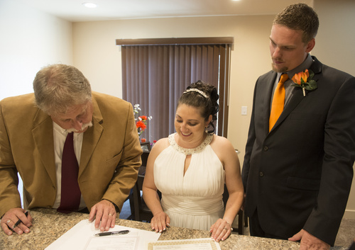 Rick Egan  |  The Salt Lake Tribune  Tribune columnist, Robert Kirby, assists Jerri Lynn Moore, and Zachary Peter Hans, in signing the marriage certificates, at their home in Herriman, Monday, July 7, 2014