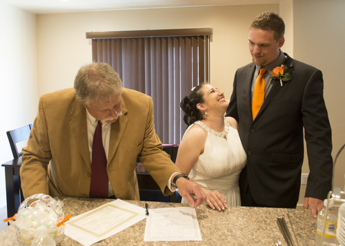 Rick Egan  |  The Salt Lake Tribune  Jerri Lynn Moore, and Zachary Peter Hans share a laugh, as Tribune columnist, Robert Kirby, assists tries to make sense of the marriage certificates, at the Han's home in Herriman, Monday, July 7, 2014.