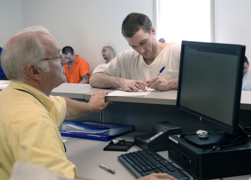 Al Hartmann  |  The Salt Lake Tribune  Prison inmate John Fowers applies at the Utah Driver License Division office set up at the Utah Prison in Draper Tuesday July 8 to receive temporary state identification documents before being released.  HB 320, passed in 2013 allows eligible individuals to get a temporary state identification document while they gather necessary papers to apply for a permanent ID. The Utah Department of Corrections and Utah Driver License Division have set up a driver license office at the Utah State Prison to provide eligible offenders with a temporary ID document on the day of their release, ensuring they leave prison with the identification they need to rejoin the community. The documents are valid for six months. The program launched July 1.