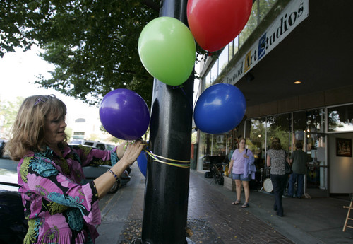 Laurie Bray of Photography by Laurie puts out balloons in front of her gallery during the Sugarhouse Art Stroll Friday, October 3, 2008 in Salt Lake City. The first-ever Sugar House art stroll was designed to invigorate the area marred by a construction crater. The free event featured live band, art exhibits, dancers.  -- 10/03/08 (Jim Urquhart/The Salt Lake Tribune)