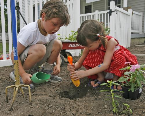 David K. McFalls, 6, helps Lela B. Howard plant a  flower in the garden of the Montessori School in Sugarhouse. photo by Rick Egan 6/29/2006