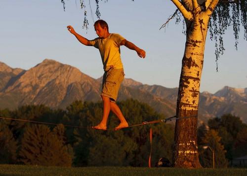 Salt Lake City - Matt Pallach works on his balance slicklining between two trees in SugarHouse Park Friday, July 17, 2009. Trent Nelson/The Salt Lake Tribune; 7.17.2009