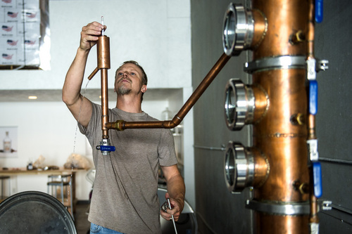 Chris Detrick  |  The Salt Lake Tribune Head distiller Chris Barlow takes a hydrometer reading while distilling Jack Rabbit Gin at Beehive Distilling, 1745 S. Milestone (3000 West), Wednesday June 25, 2014. Beehive distills Jack Rabbit Gin, which is available to purchase at the State Liquor Stores.