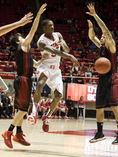 JIM MCAULEY | The Salt Lake Tribune Utah's Delon Wright passes the ball under pressure from the St. Katherine Firebirds at the University of Utah's Huntsman Center on December 28, 2013.