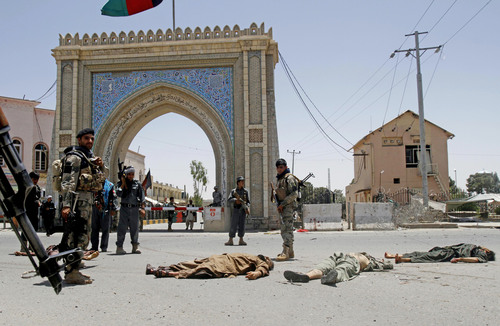 Afghan security forces stand guard near the dead bodies of Taliban fighters at the site of a suicide attack in the city of Kandahar, Afghanistan, Wednesday, July 9, 2014. In an attack early Wednesday against the governor's compound in the southern city of Kandahar, several people, including two police officers were killed when insurgents wearing bomb vests tried to take over the small complex.(AP Photo/Allauddin Khan)