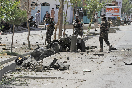 Afghanistan's security forces inspect the site of a suicide attack in the city of Kandahar, south of Kabul, Afghanistan, Wednesday, July 9, 2014.  In an attack early Wednesday against the governor's compound in the southern city of Kandahar, several people, including two police officers were killed when insurgents wearing bomb vests tried to take over the small complex. (AP Photo/Allauddin Khan)