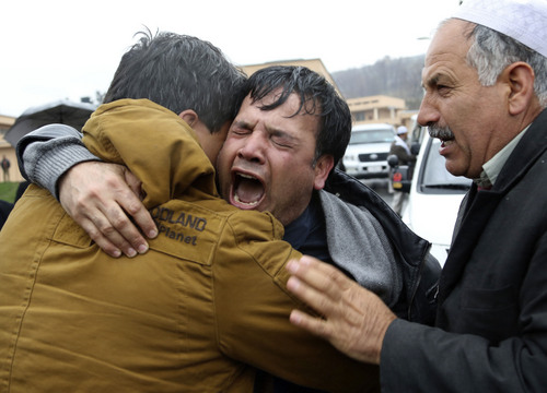 FILE - In this Sunday, March 23, 2014 file photo, Bashir Ahmad, center, brother of killed Agence France-Press journalist Sardar Ahmad cries during his brother's funeral ceremony in Kabul, Afghanistan. Sardar, his wife and two of his young children were killed when four gunmen attacked the Serena hotel in Kabul during New Year's celebrations on March 20, 2014. The number of Afghan civilians, including children, killed in violence rose by nearly 17 percent in the first half of this year, compared with the same period in 2013 as the fight is increasingly taking place closer to homes in populated areas, the U.N. said Wednesday, July 9, 2014.(AP Photo/Rahmat Gul, File)
