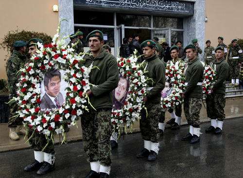 FILE- In this Sunday, March 23, 2014 file photo, Afghan honor guards carry wreaths with photographs of Agence France-Press journalist Sardar Ahmad, his wife Humaira and their children Nilofar and Omar during their funeral ceremony in Kabul, Afghanistan,. Sardar and his family were killed when four gunmen attacked the Serena hotel in Kabul during New Year's celebrations on March 20, 2014. The number of Afghan civilians, including children, killed in violence rose by nearly 17 percent in the first half of this year, compared with the same period in 2013 as the fight is increasingly taking place closer to homes in populated areas, the U.N. said Wednesday, July 9, 2014.(AP Photo/Rahmat Gul, File)