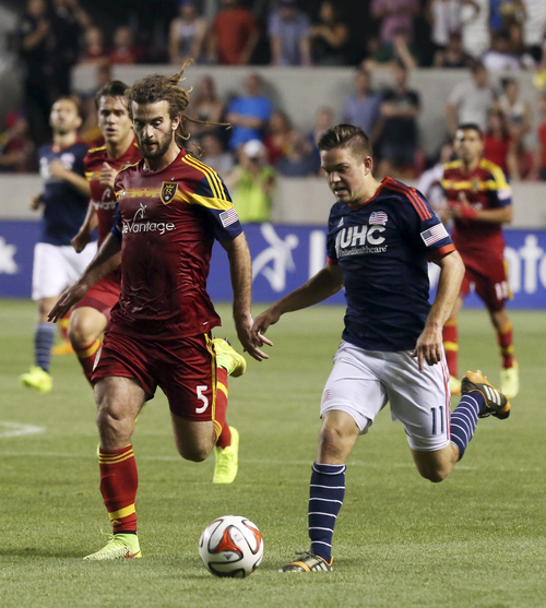 Real Salt Lake midfielder Kyle Beckerman (5) chases as New England Revolution midfielder Kelyn Rowe (11) dribbles down the field in the second half of an MLS soccer match, Friday, July 4, 2014, in Sandy, Utah. Real Salt Lake went on to win the match 2-1. (AP Photo/Kim Raff)