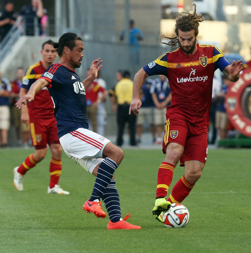 Real Salt Lake midfielder Kyle Beckerman, right, dribbles past New England Revolution midfielder Daigo Kobayashi, left, in the first half of an MLS soccer match on Friday, July 4, 2014, in Sandy, Utah. (AP Photo/Kim Raff)