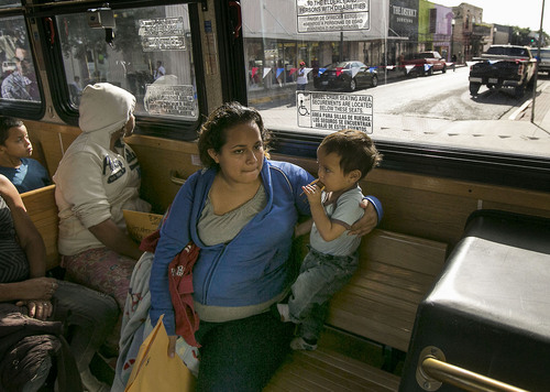 In this photo taken July 4, 2014, Marta Beltran, 19, of El Salvador, holds her 18-month-old son, Lenny, as they ride a city shuttle bus from the McAllen city bus station to the Sacred Heart Catholic Church Shelter in McAllen, Texas. About 90 Hondurans a day cross illegally from Mexico into the U.S. at the Rio Grande near McAllen, according to the Honduran Consulate, and the families are then brought to Central Station in McAllen and each is released on their own recognizance. Though most travelers have enough money to purchase their own bus tickets to meet family in cities across the U.S., many have nowhere to stay before the buses leave, and most are in need of rest, medical attention and sustenance. It falls to the local government and charities to welcome the uninvited visitors to America. Tens of thousands have also fled to the U.S. from El Salvador and Guatemala to escape violence.  (AP Photo/Austin American-Statesman, Rodolfo Gonzalez)