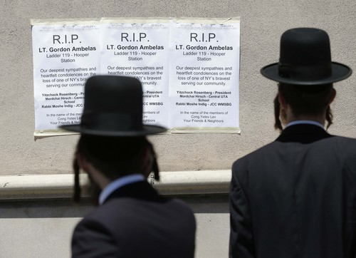 Signs commemorating Lt. Gordon Ambelas are displayed across the street from a firehouse in New York, Sunday, July 6, 2014. The Fire Department of New York is mourning the death of Ambelas, who became trapped while looking for victims in a public-housing high-rise blaze, the first to die in the line of duty in more than two years. Ambelas died Saturday after suffering multiple injuries while on the 19th floor of the 21-story building in the Williamsburg section of Brooklyn, officials said. (AP Photo/Seth Wenig)