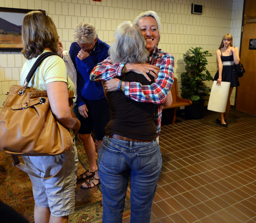 Supporters of Boulder County Clerk and Recorder Hillary Hall hug outside the courtroom at the Boulder County Justice Center on Wednesday, July 9, 2014 in Boulder, Colo. Hall, is in court to respond to a suit brought by Colorado Attorney General John Suthers who wants the court to issue an injunction to stop the county from issuing marriage licenses to same-sex couples. (AP Photo/Daily Camera, Cliff Grassmick)