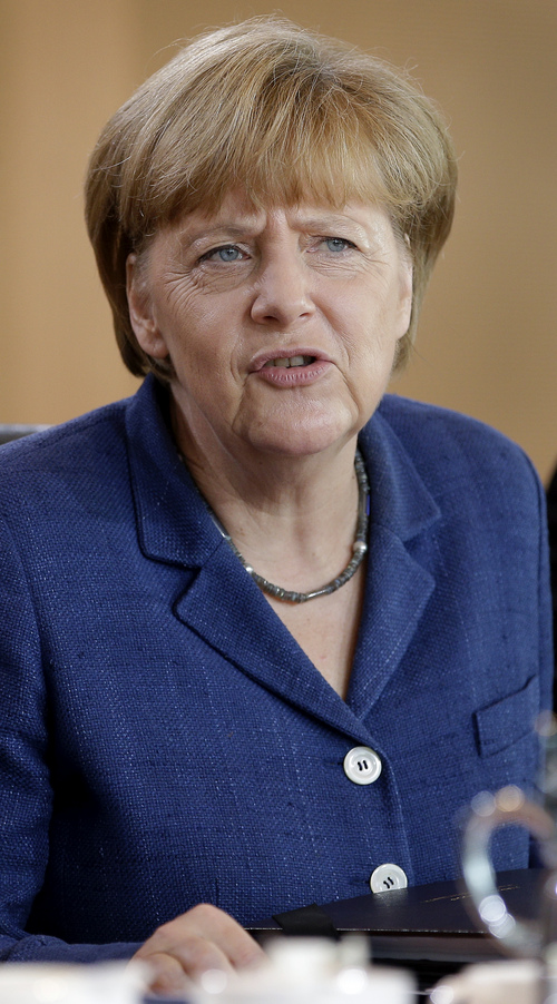 German Chancellor Angela Merkel speaks as she arrives for the weekly cabinet meeting at the chancellery in Berlin, Germany, Wednesday, July 9, 2014. (AP Photo/Michael Sohn)