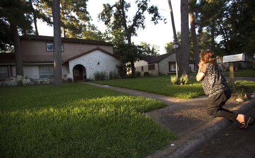 Patti Beller prays Thursday, July 10, 2014, in Spring, Texas, outside the home that was the scene of a multiple shooting the night before. The Harris County Sheriff's Office says Ronald Lee Haskell was booked Thursday on a capital murder/multiple murders charge and held without bond. Authorities believe Haskell fatally shot two adults and four children on Wednesday night and critically wounded a 15-year-old girl, who called 911. (AP Photo/Houston Chronicle, Cody Duty) MANDATORY CREDIT