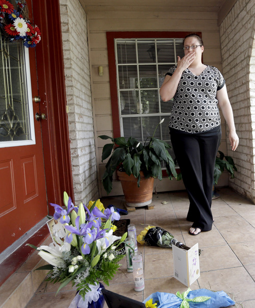 Neighbor Kristen Breelove pauses after leaving flowers on the porch of a home Thursday, July 10, 2014, in Spring, Texas. where six family members were shot to death the night before. The Harris County Sheriff's Office says Ronald Lee Haskell was booked Thursday on a capital murder/multiple murders charge and held without bond. Authorities believe Haskell fatally shot two adults and four children on Wednesday night and critically wounded a 15-year-old girl, who called 911.  (AP Photo/David J. Phillip)