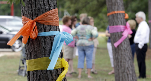 Faculty and parents gather outside Lemm Elementary School after placing ribbons on the trees in honor of those killed in a multiple shooting Thursday, July 10, 2014, in Spring, Texas. Some of the victims were students at the school. The Harris County Sheriff's Office says Ronald Lee Haskell was booked Thursday on a capital murder/multiple murders charge and held without bond. Authorities believe Haskell fatally shot two adults and four children on Wednesday night and critically wounded a 15-year-old girl, who called 911.(AP Photo/David J. Phillip)