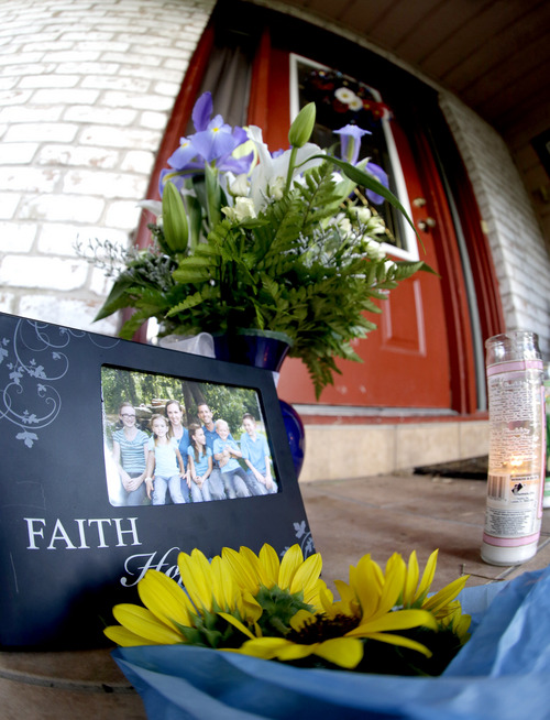 A photograph, flowers and candles are left on the porch where a fatal home shooting took place Thursday, July 10, 2014, in Spring, Texas. The Harris County Sheriff's Office says Ronald Lee Haskell was booked Thursday on a capital murder/multiple murders charge and held without bond. Authorities believe Haskell fatally shot two adults and four children on Wednesday night and critically wounded a 15-year-old girl, who called 911.  (AP Photo/David J. Phillip)