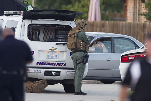 Law enforcement officers surround a shooting suspect in his car Wednesday, July 9, 2014, in Spring, Texas. Deputies cornered the suspect in a shooting at a suburban Houston home that resulted in multiple fatalities. (AP Photo/Houston Chronicle, Brett Coomer)