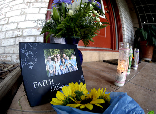 A photograph, flowers and candles are left on the porch where a fatal home shooting took place Thursday, July 10, 2014, in Spring, Texas. The Harris County Sheriff's Office says Ronald Lee Haskell was booked Thursday on a capital murder/multiple murders charge and held without bond.  Haskell surrendered Wednesday night to end the domestic dispute in Spring. Authorities believe Haskell fatally shot two adults and four children and critically wounded a 15-year-old girl, who called 911.   (AP Photo/David J. Phillip)