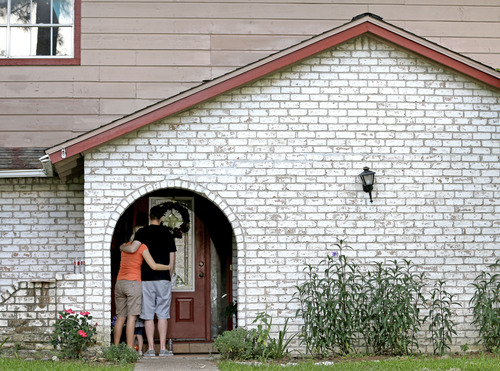 A family who identified themselves as friends of the victims, pause on the porch Thursday, July 10, 2014, after placing flowers and a framed photograph at the door of the home where a gunman killed six people Wednesday in Spring, Texas. The Harris County Sheriff's Office says Ronald Lee Haskell was booked Thursday on a capital murder/multiple murders charge and held without bond. Haskell surrendered Wednesday night to end the domestic dispute in Spring. Authorities believe Haskell fatally shot two adults and four of his children and critically wounded his 15-year-old daughter, who called 911.   (AP Photo/David J. Phillip)