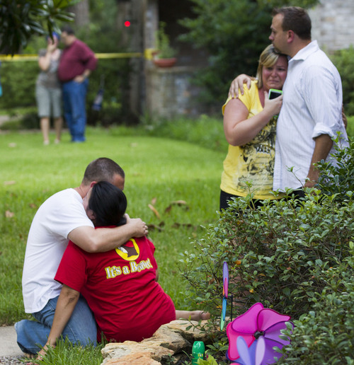 Neighbors embrace each other following a shooting Wednesday, July 9, 2014, in Spring, Texas. Deputies have cornered a man suspected in a shooting at a suburban Houston home that resulted in multiple fatalities. (AP Photo/Houston Chronicle, Brett Coomer)