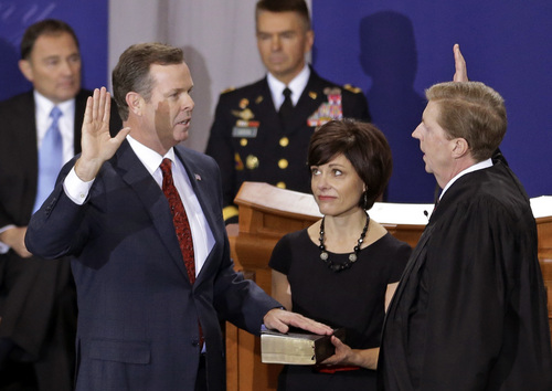 FILE - This Jan. 7, 2013 file photo shows Utah Attorney General John Swallow, left, being sworn in by Chief Justice Matthew B. Durrant, right, at the Utah Sate Capitol Rotunda, in Salt Lake City. Leaders at the Utah legislature plan to spend their June caucus meeting formally discussing the possibility of impeaching embattled Attorney General John Swallow. (AP Photo/Rick Bowmer, File)