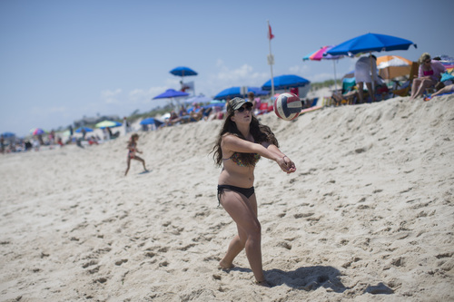 In this photo taken on Friday, July 11, 2014, a beachgoer strikes a volleyball in Southampton, N.Y. Studies show the gap separating the rich from the working poor has been ever-widening in recent years and few places provide that evidence as starkly as Long Island's Hamptons. (AP Photo/John Minchillo)