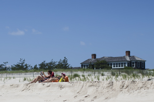 In this photo taken on Friday, July 11, 2014, beachgoers relax near a beachfront property in Southampton, N.Y. Studies show the gap separating the rich from the working poor has been ever-widening in recent years and few places provide that evidence as starkly as Long Island's Hamptons. (AP Photo/John Minchillo)