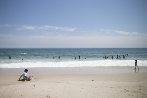 In this photo taken on Friday, July 11, 2014, beachgoers enjoy the surf in Southampton, N.Y. Studies show the gap separating the rich from the working poor has been ever-widening in recent years and few places provide that evidence as starkly as Long Island's Hamptons. (AP Photo/John Minchillo)