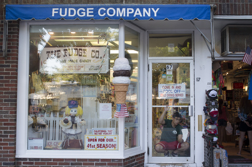 In this photo taken on Friday, July 11, 2014, a worker cleans the door to The Fudge Company in Southampton, N.Y. Studies show the gap separating the rich from the working poor has been ever-widening in recent years and few places provide that evidence as starkly as Long Island's Hamptons. (AP Photo/John Minchillo)