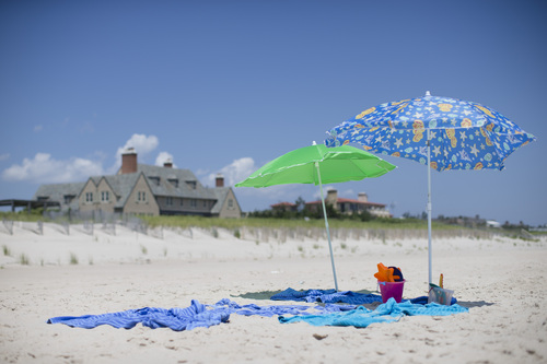 In this photo taken on Friday, July 11, 2014, beach umbrellas stand unattended outside a private residence in Southampton, N.Y. Studies show the gap separating the rich from the working poor has been ever-widening in recent years and few places provide that evidence as starkly as Long Island's Hamptons. (AP Photo/John Minchillo)