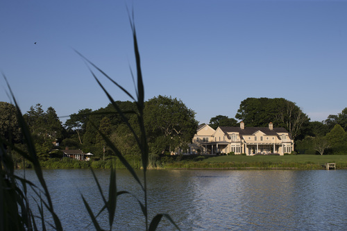 In this photo taken on Friday, July 11, 2014, a private residence overlooks an inlet in Southampton, N.Y. Studies show the gap separating the rich from the working poor has been ever-widening in recent years and few places provide that evidence as starkly as Long Island's Hamptons. (AP Photo/John Minchillo)