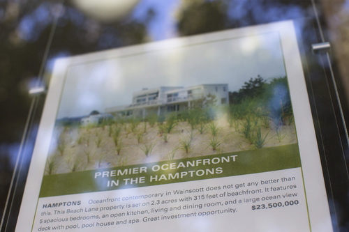 In this photo taken on Friday, July 11, 2014, a local real estate listing for a oceanfront property going for $23.5 million is displayed in Southampton, N.Y. Studies show the gap separating the rich from the working poor has been ever-widening in recent years and few places provide that evidence as starkly as Long Island's Hamptons. (AP Photo/John Minchillo)