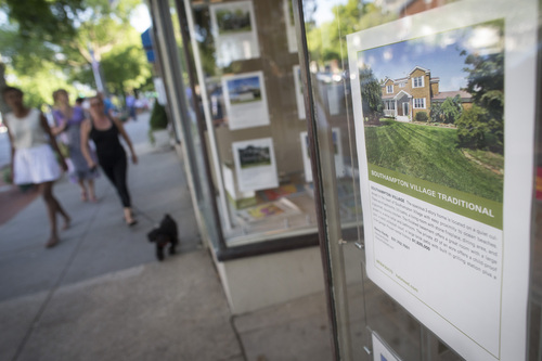 In this photo taken on Friday, July 11, 2014, pedestrians pass a real estate sales office displaying listings that exceed $1 million in Southampton, N.Y. Studies show the gap separating the rich from the working poor has been ever-widening in recent years and few places provide that evidence as starkly as Long Island's Hamptons. (AP Photo/John Minchillo)