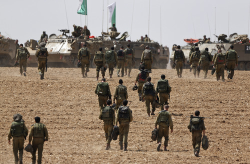 Israeli infantry soldiers walk to their armored personnel carriers to take up new positions on the Israel-Gaza border, Saturday, July 12, 2014. Israeli airstrikes overnight targeting Hamas in Gaza hit a mosque its military says concealed the militant group's weapons, in an offensive that showed no signs of slowing down. Israel launched its campaign five days ago to stop relentless rocket fire on its citizens. While there have been no fatalities in Israel, Palestinian officials said overnight attacks raised the death toll there to over 120, with more than 920 wounded. (AP Photo/Lefteris Pitarakis)
