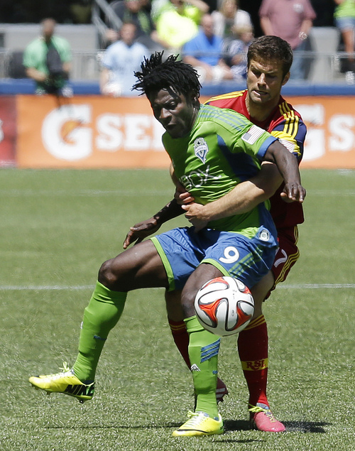 Real Salt Lake's Chris Wingert, right, holds Seattle Sounders's Obafemi Martins (9) as they battle for the ball in the first half of an MLS soccer match, Saturday, May 31, 2014, in Seattle. (AP Photo/Ted S. Warren)