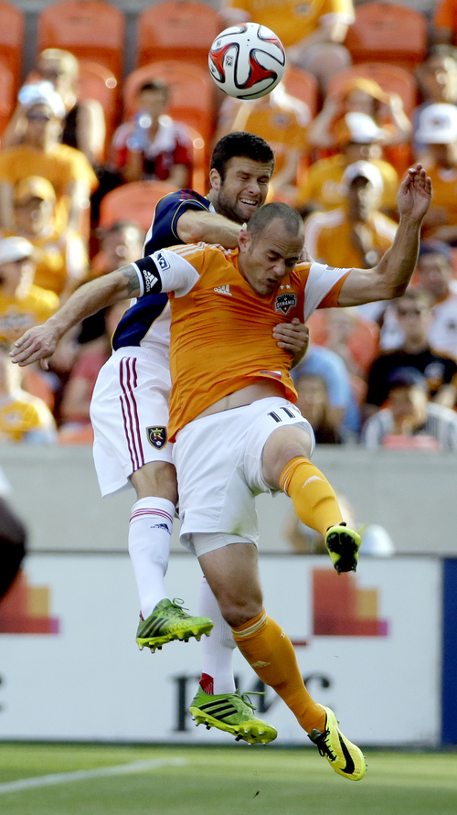 Houston Dynamo's Brad Davis (11) and Real Salt Lake's Chris Wingert go up for the ball during the first half of an MLS soccer game on Sunday, May 11, 2014, in Houston. (AP Photo/David J. Phillip)