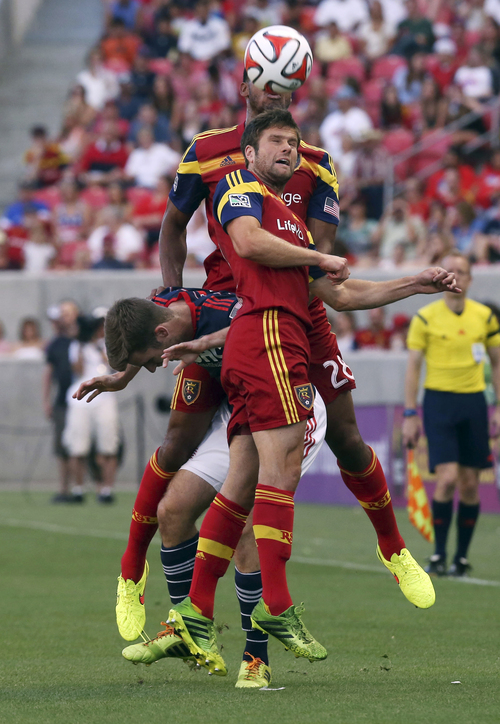 Real Salt Lake defender Chris Wingert, front, and Real Salt Lake defender Chris Schuler (28) overtake New England Revolution forward Patrick Mullins, middle, for a head ball in the first half of an MLS soccer match, Friday, July 4, 2014, in Sandy, Utah. Real Salt Lake went on to win the match 2-1. (AP Photo/Kim Raff)