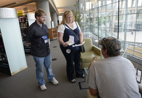 Al Hartmann  |  The Salt Lake Tribune  The Volunteers of America library engagement team's Jen Page and Ethan Sellers introduce themselves to a homeless person in the Salt Lake City Library. They told him how Volunteers of America can help him and direct him to services.  He was looking for a job and they had suggestions on how to help.