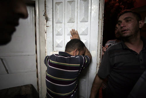 """Palestinians mourn their relatives in the morgue of the Shifa hospital in Gaza City on Saturday, July 12, 2014. Over a dozen Palestinians were killed in an Israeli strike on a house, hospital officials said. Ignoring international appeals for a cease-fire, Israel on Saturday widened its range of Gaza bombing targets to civilian institutions with suspected Hamas ties and announced it would hit northern Gaza """"with great force"""" to prevent rocket attacks from there on Israel. (AP Photo/Khalil Hamra)"""