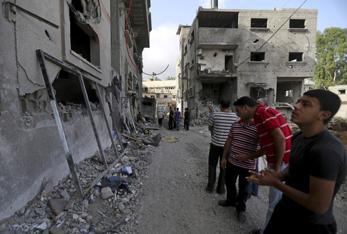 Palestinians gather outside the damaged house of Gaza's police chief Taysir al-Batsh after it was hit by an Israeli missile strike in Gaza City, Sunday, July 13, 2014. The strike that hit the home and damaged a nearby mosque as evening prayers ended Saturday, killed at least 18 people, wounded  50 and left some people believed to be trapped under the rubble, said Palestinian Health Ministry official Ashraf al-Kidra. (AP Photo/Hatem Moussa