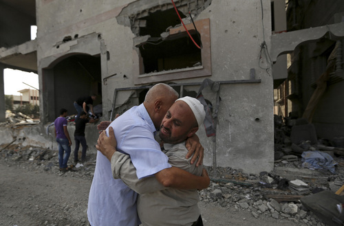Palestinians give greetings in front of the damaged house of Gaza's police chief Taysir al-Batsh after it was hit by an Israeli missile strike in Gaza City, Sunday, July 13, 2014. The strike that hit the home and damaged a nearby mosque as evening prayers ended Saturday, killed at least 18 people, wounded 50 and left some people believed to be trapped under the rubble, said Palestinian Health Ministry official Ashraf al-Kidra. (AP Photo/Hatem Moussa