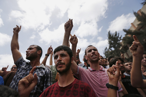 Palestinian mourners chant slogans during a funeral procession of a member of the al-Batsh family who were killed in Saturday's Israeli airstrike, during a funeral procession in Gaza City on Sunday, July 13, 2014. The strike hit the home of Gaza police chief Taysir al-Batsh and damaged a nearby mosque as evening prayers ended Saturday, killing at least 18 people, wounding 50 and leaving some people believed to be trapped under the rubble, said Palestinian Health Ministry official Ashraf al-Kidra. (AP Photo/Lefteris Pitarakis)