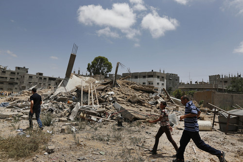 Palestinians walk past one of the houses of the al-Batsh family, demolished by an Israeli strike earlier last week, as they rush to the funeral procession of several members of the al-Batsh family who were killed in Saturday's Israeli airstrike, during a funeral procession in Gaza City on Sunday, July 13, 2014. The strike hit the home of Gaza police chief Taysir al-Batsh and damaged a nearby mosque as evening prayers ended Saturday, killing at least 18 people, wounding 50 and leaving some people believed to be trapped under the rubble, said Palestinian Health Ministry official Ashraf al-Kidra. (AP Photo/Lefteris Pitarakis)