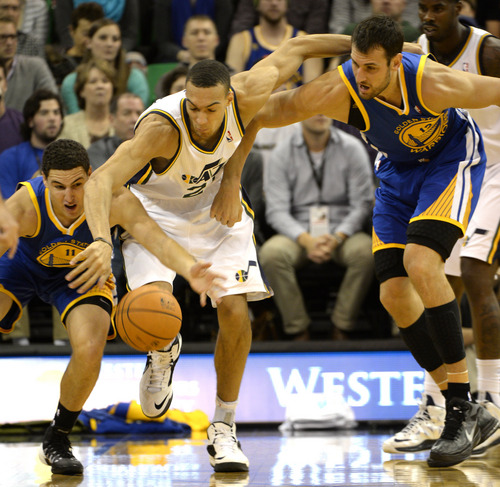 Rick Egan    The Salt Lake Tribune   Utah Jazz center Rudy Gobert (27) goes for a loose ball along with Golden State Warriors shooting guard Klay Thompson (11) and Golden State Warriors center Andrew Bogut (12), as The Utah Jazz faced The Golden State Warriors, at the EnergySolutions Arena, Monday, November 18, 2013.  Curry did not return to the game after the play.