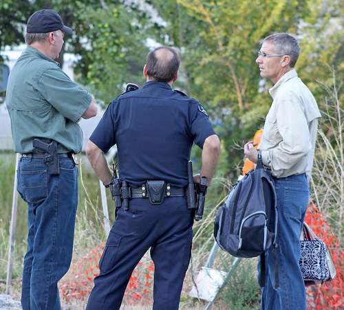 Cache County Attorney James Swink confers with Logan City police officers Monday, July 14, 2014, at the scene where two gunshot victims were found in Logan, Utah. Police say three people have been found shot dead in two different locations in Logan. Police say they responded to reports of gunfire at an apartment just after midnight.   Police say they found a man and a woman dead inside one of the units. Officers say they received another 911 call around 1 a.m. reporting a gunshot at a west Logan home and found a man dead of what appears to be a self-inflicted gunshot wound. Police suspect the two incidents are connected.  (AP Photo/The Herald Journal,Amy Macavinta)